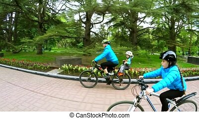 Active Mother With Two Children Cycling In Green Park