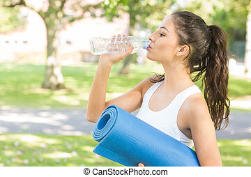Active peaceful brunette holding exercise mat in a park on a...