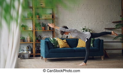 Active person is doing yoga at home practising balance...