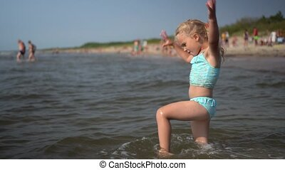 Active playful little girl dance wading through sea water waves. Funny child