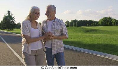 Active positive seniors enjoying a walk in park