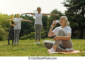 Active retired lady drinking water after intensive workout
