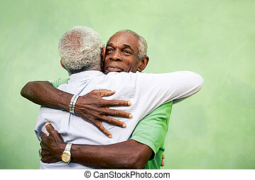 Active retired old men and leisure, two senior black brothers hugging outdoors