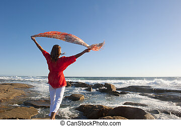Beautiful senior woman enjoying active retirement and happy leisure lifestyle at seaside, with ocean and blue sky as background and copy space.