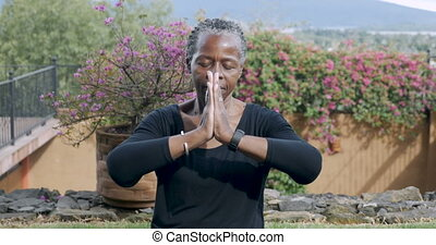 Active senior African American woman putting her hands together in a namaste