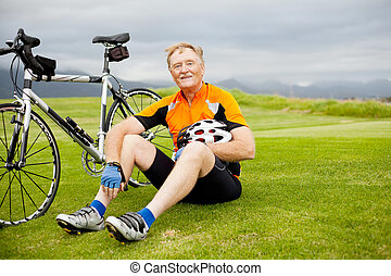 active senior bicyclist taking a break on the hill
