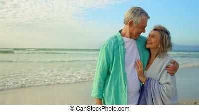 Active senior Caucasian couple embracing each other on the ...