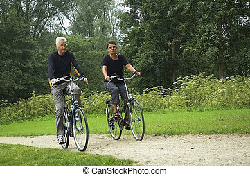 Active senior couple biking in the park.