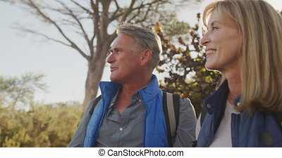 Active senior couple hiking in forest