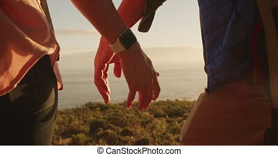Active senior couple holding hands in forest