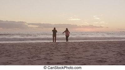 Active senior couple jumping on beach