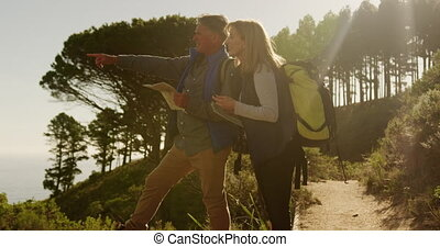 Active senior couple looking map in forest - Side view of a ...