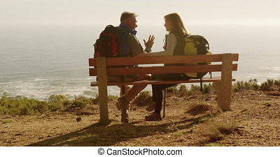 Active senior couple sitting on bench in forest