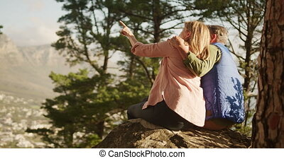Active senior couple sitting on rock in forest