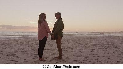 Active senior couple standing on beach