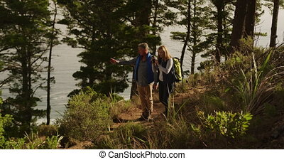 Active senior couple taking picture in forest - Front view ...
