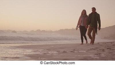 Active senior couple walking on beach