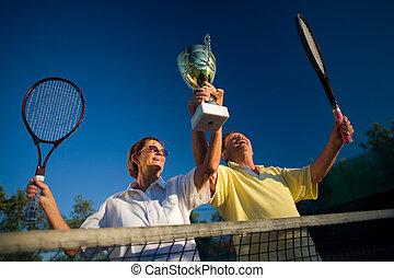 Active senior couple win - Active senior couple is posing on...