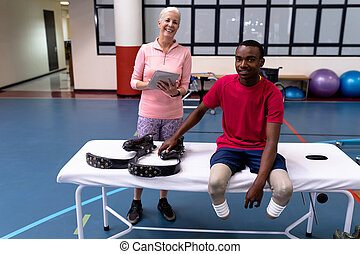 Active senior female trainer and disabled man looking at camera in sports center