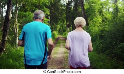 Active senior man and woman running for better fitness in a forest