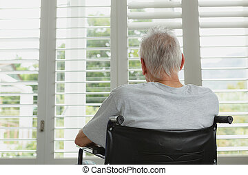Active senior man in wheelchair looking through window at home