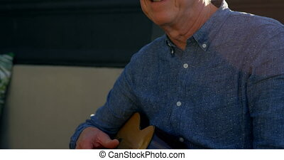 Active senior man playing guitar in the balcony at home 4k