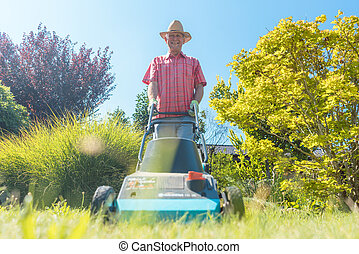 Active senior man smiling while using a grass cutting machine