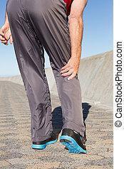 Active senior man touching his injured knee