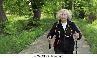 Active senior old woman training Nordic walking with ski ...
