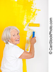 Active senior painting a wall