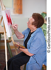 Active senior paints a picture in Leisure - Old woman paints...
