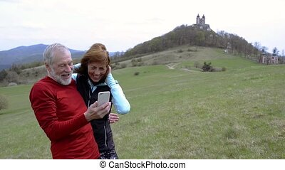 Active senior runners in nature looking at pictures in smart...