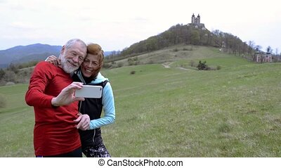 Active senior runners in nature taking selfie with smart phone.