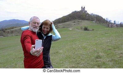 Active senior runners in nature taking selfie with smart...