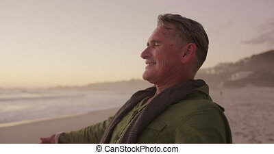 Active senior standing on beach - Side view close up of a ...