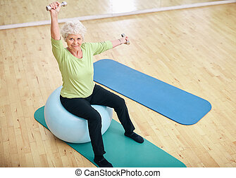 Active senior woman at gym exercising with weights - Active...