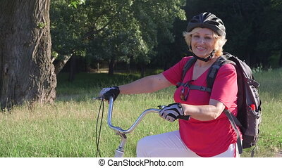 Active senior woman cyclist on bicycle looking at camera smiling