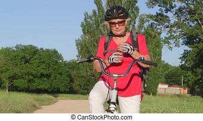 Active senior woman cyclist on bicycle