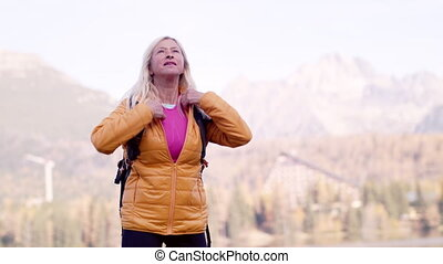 Active senior woman hiker standing outdoors in nature, ...