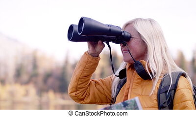 Active senior woman hiker with binoculars standing outdoors in nature.