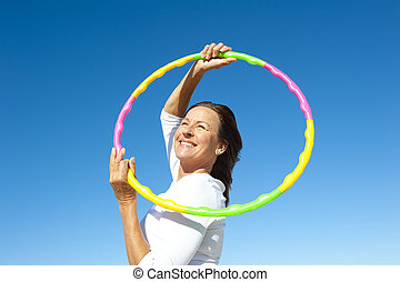 Active senior woman hula hoop exercise - Portrait of happy ...