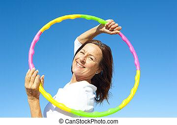 Active senior woman hula hoop exercise