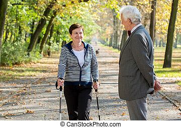Active senior woman nordic walking in park