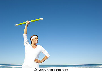 Active senior woman ocean background