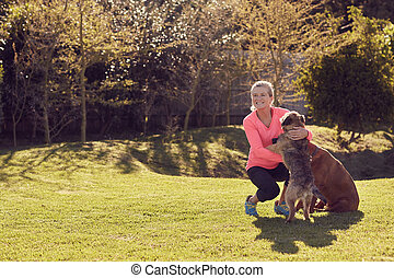 Active senior woman petting her dogs outside in a garden -...