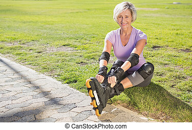 Active senior woman ready to go rollerblading on a sunny day