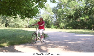 Active senior woman riding bicycle in park on sunny day - ...