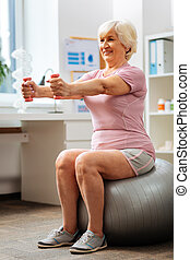 Active senior woman sitting on the fitness ball