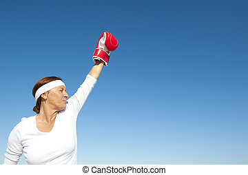 Active senior woman sky background
