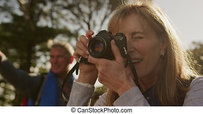 Active senior woman taking picture in forest - Front view ...